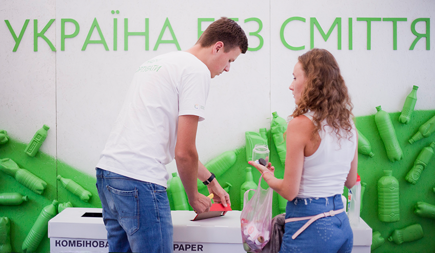 Young man and woman both wearing white tops and blue jeans stand in front of recycling bin and sort their waste