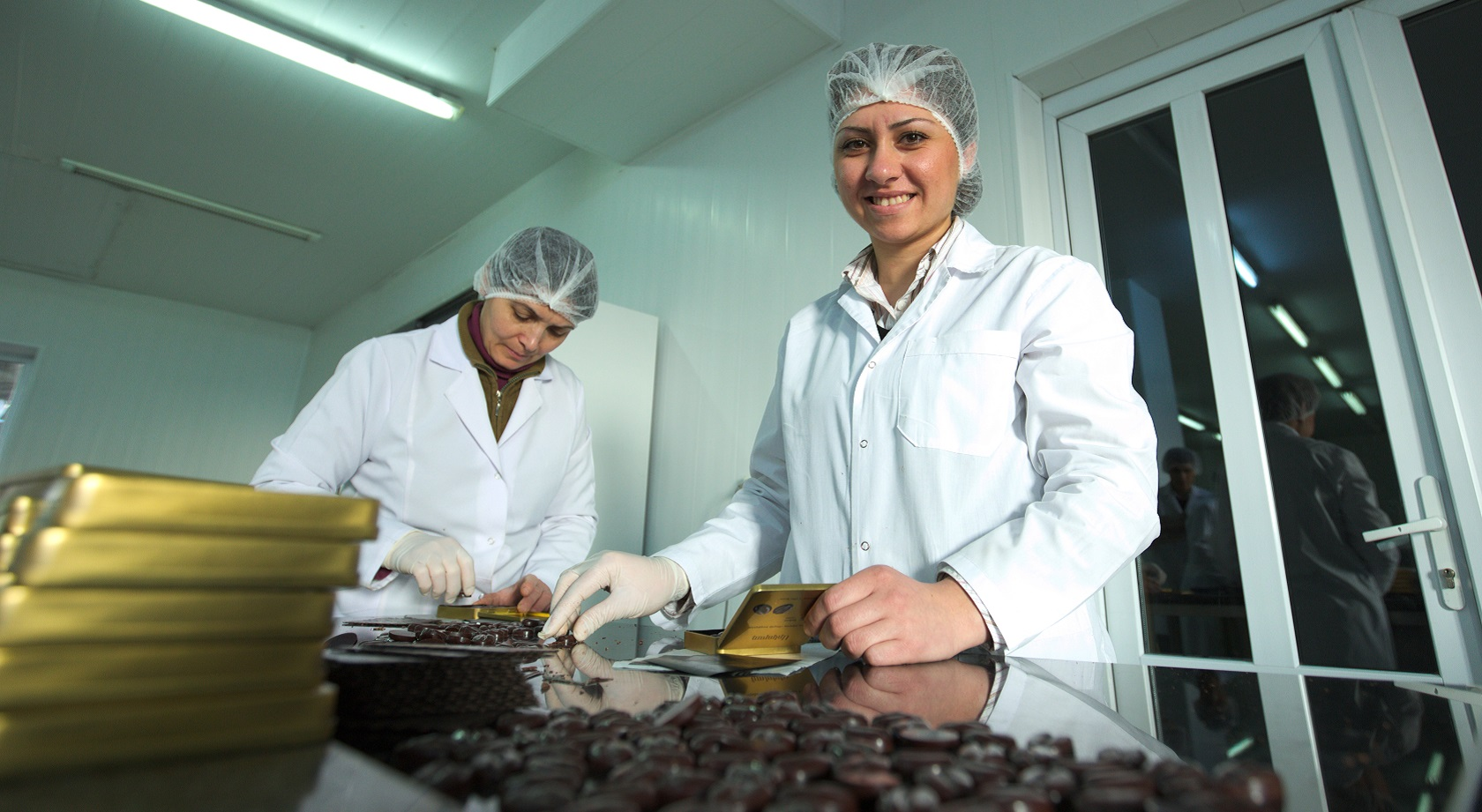 Two women wearing hair nets and white jackets working in chocolate factory
